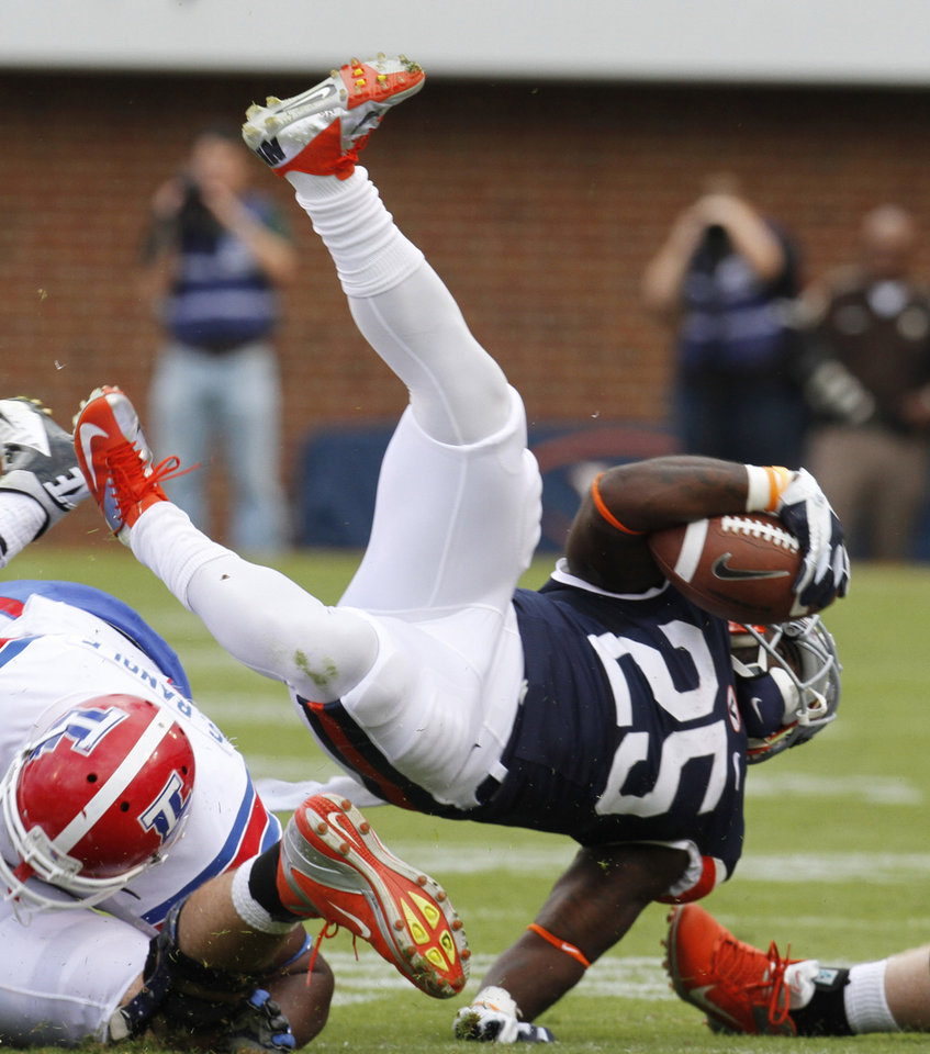 Virginia running back Kevin Parks (25) is upended during the first half of an NCAA college football game against Louisiana Tech in Charlottesville, Va., Saturday, Sept. 29, 2012. (AP Photo/Steve Helber)