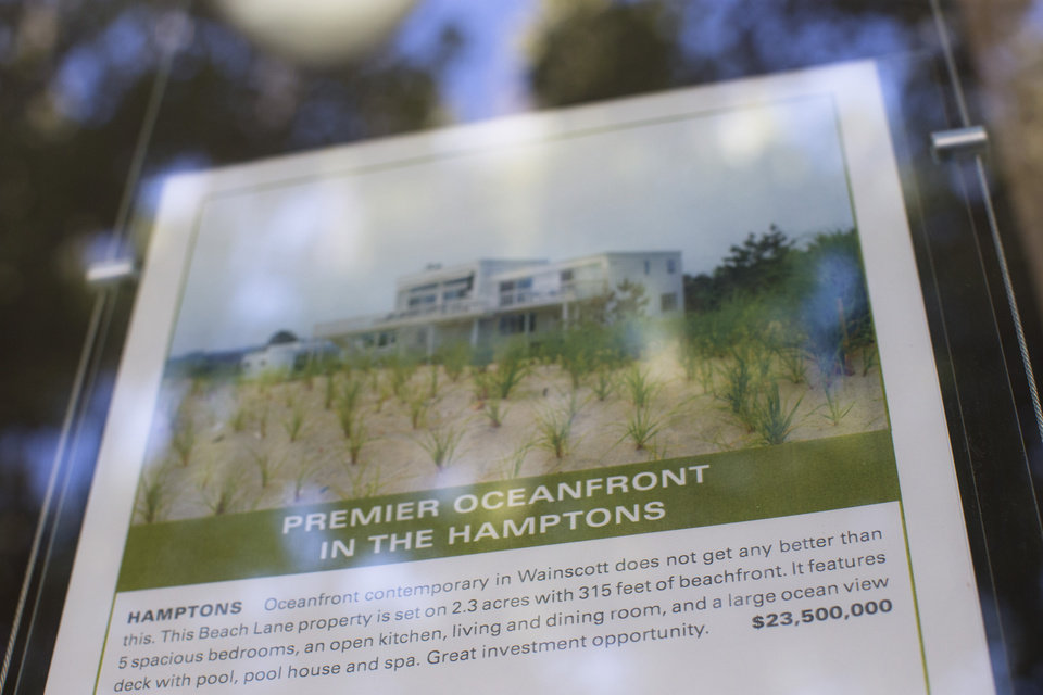 Photo - In this photo taken on Friday, July 11, 2014, a local real estate listing for a oceanfront property going for $23.5 million is displayed in Southampton, N.Y. Studies show the gap separating the rich from the working poor has been ever-widening in recent years and few places provide that evidence as starkly as Long Island's Hamptons. (AP Photo/John Minchillo)