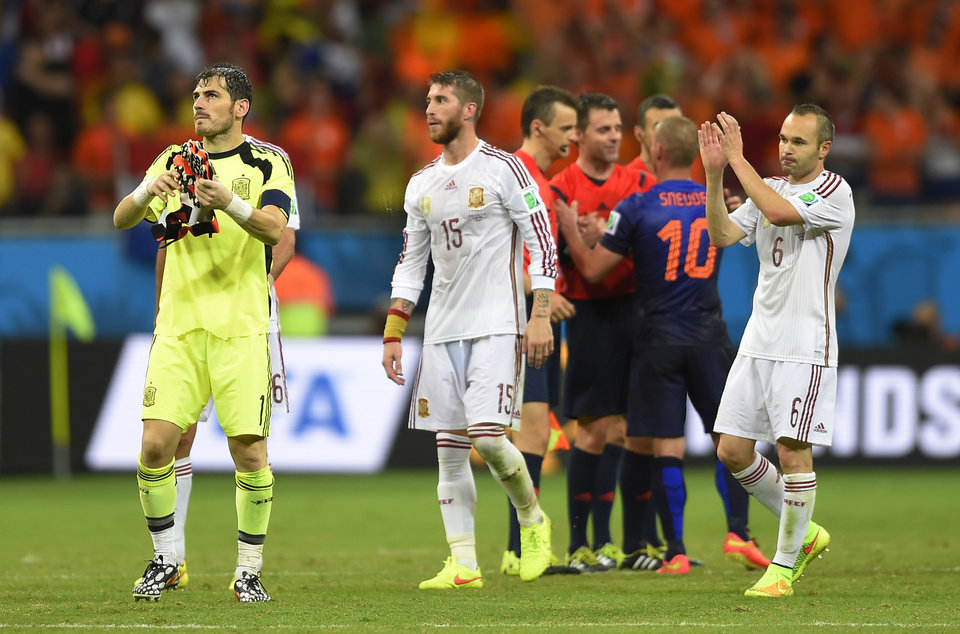 Photo - Spain's goalkeeper Iker Casillas, left, Spain's Sergio Ramos, centre and Spain's Andres Iniesta react after the group B World Cup soccer match between Spain and the Netherlands at the Arena Ponte Nova in Salvador, Brazil, Friday, June 13, 2014.  The Netherlands won the match 5-1. (AP Photo/Manu Fernandez)