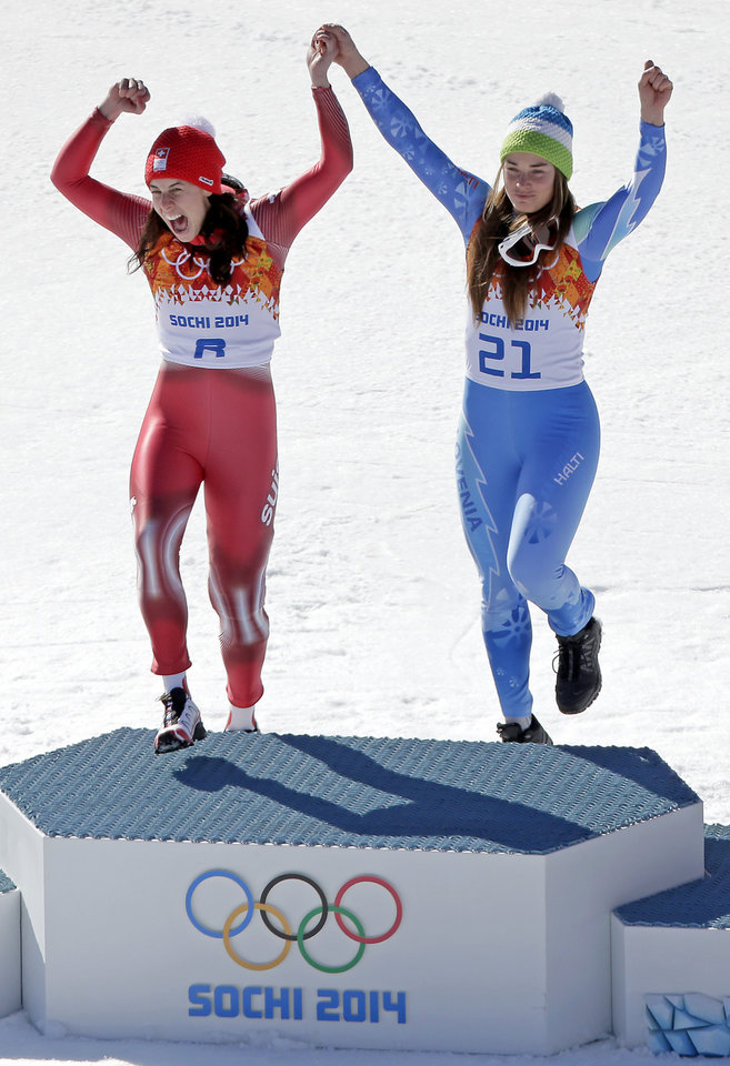 Photo - Women's downhill gold medal winners Switzerland's Dominique Gisin, left, and Slovenia's Tina Maze step onto the podium together during a flower ceremony at the Sochi 2014 Winter Olympics, Wednesday, Feb. 12, 2014, in Krasnaya Polyana, Russia. (AP  Photo/Charlie Riedel)