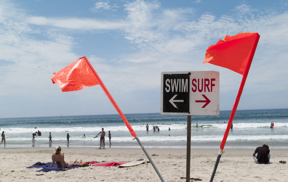 Photo - Warning flags are set on the beach as people enjoy Venice Beach in Los Angeles Monday, July 28, 2014. Los Angeles' popular Venice Beach teemed with people enjoying a weekend outing on the boardwalk and sand when lifeguards and other witnesses say lightning from a rare summer thunderstorm hit without warning, injuring or rattling more than a dozen people and leaving a 21-year-old man dead. The witnesses said the strike hit with a tremendous boom about 2:30 p.m. Sunday, July 27, rattling buildings and showering a lifeguard headquarters with sparks. (AP Photo/Damian Dovarganes)