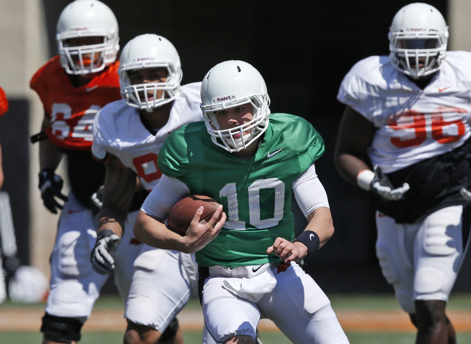 Photo - Oklahoma State quarterback Mason Rudolph (10) carries the ball during an Orange Blitz NCAA college spring football practice in Stillwater, Okla., Saturday, April 5, 2014. (AP Photo/Sue Ogrocki)