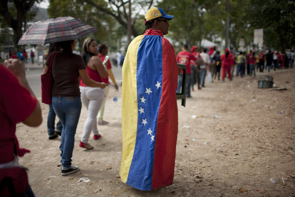 Photo - People queue outside the military academy to see the body of Venezuela's late President Hugo Chavez lying in state in Caracas, Venezuela, Sunday, March 10, 2013. Chavez died of cancer on March 5. He was 58. (AP Photo/Ariana Cubillos)