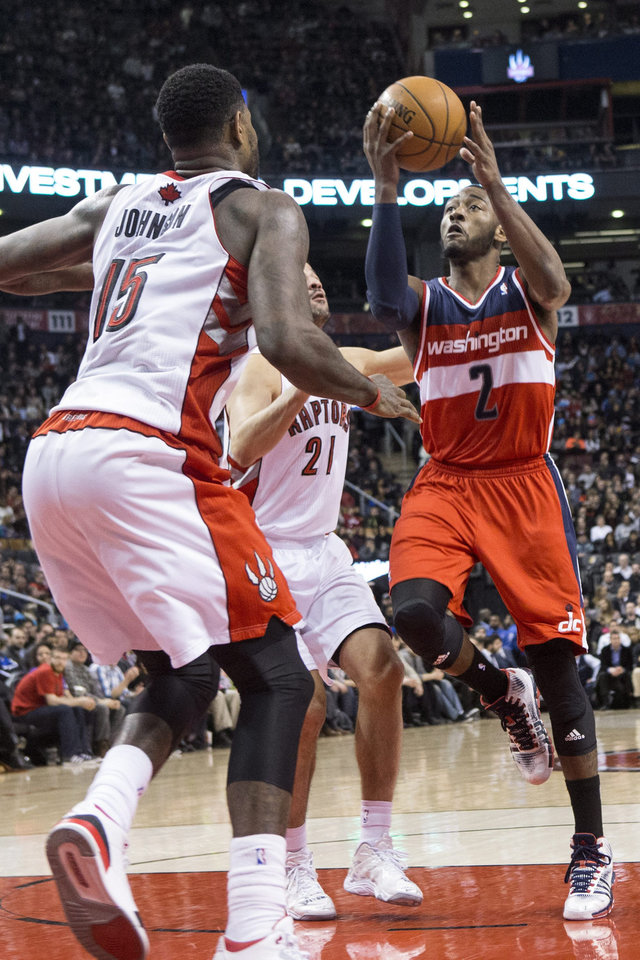 Photo - Washington Wizards' John Wall, right, scores on Toronto Raptors' Amir Johnson, left, and Greivis Vasquez during first half NBA basketball action in Toronto, Thursday, Feb. 27, 2014. (AP Photo/The Canadian Press, Chris Young)