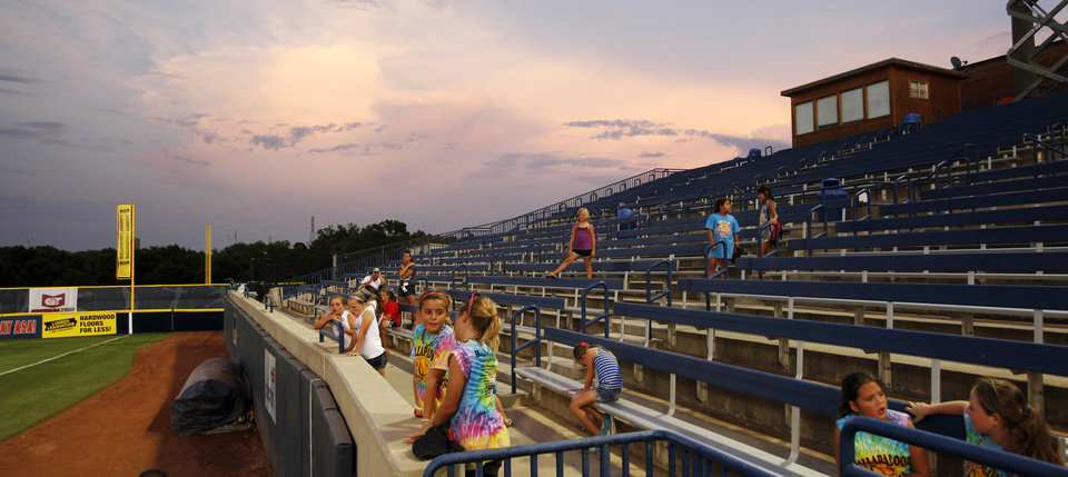 Photo - Children watch from the stands near right field as the sun sets during a game between Team USA and Canada in the World Cup of Softball at ASA Hall of Fame Stadium in Oklahoma City, Thursday, July 11, 2013. Team USA won 7-0 in 6 innings. Photo by Nate Billings, The Oklahoman