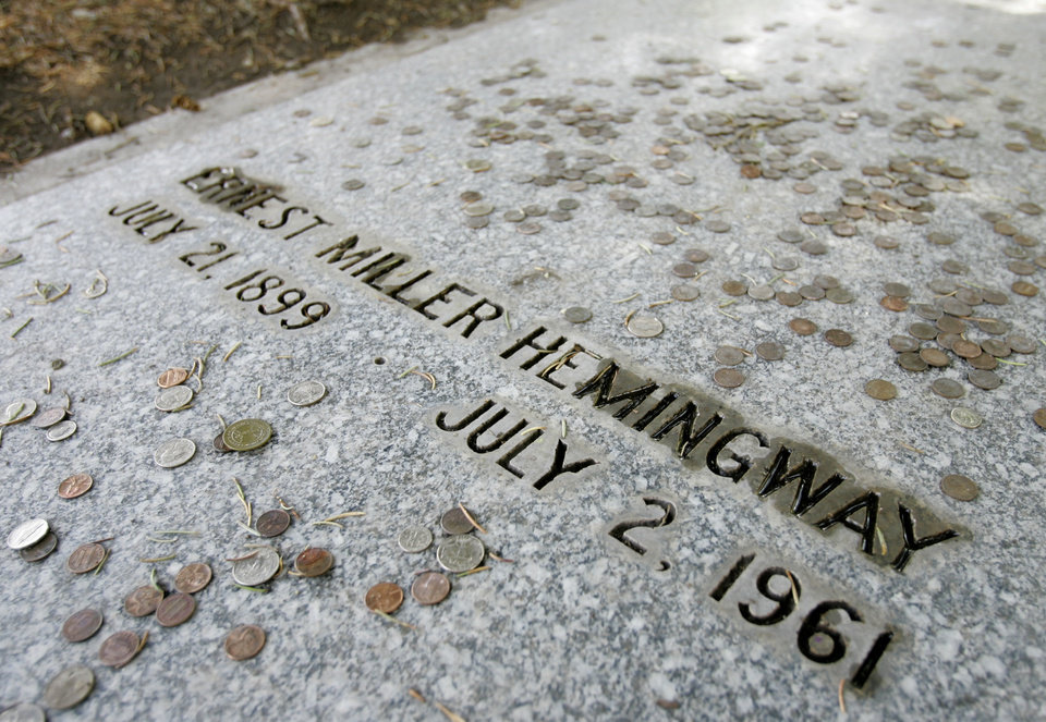 Photo - FILE - This July 30, 2007 file photo shows coins left by visitors at the grave of Ernest Hemingway in Ketchum, Idaho. The house nearby in Ketchum that was owned by the famed novelist now belongs to the Nature Conservancy as part of a private preserve. There are sites connected to Hemingway in many different locales including Florida, Cuba, Arkansas, Idaho and Illinois (AP Photo/Ted S. Warren, File)