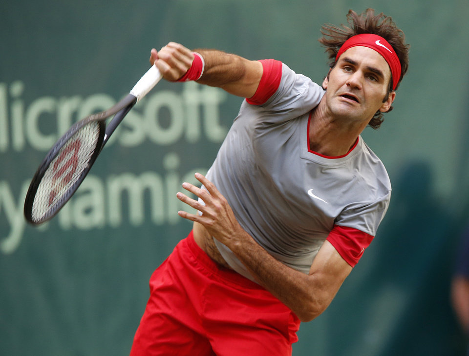 Photo - Switzerland's Roger Federer serves against Japan's Kei Nishikori during their semifinal match of the the Gerry Weber Open tennis tournament in Halle, Germany, Saturday, June 14, 2014. Federer won the match with 6-3 and 7-6. (AP Photo/Michael Probst)