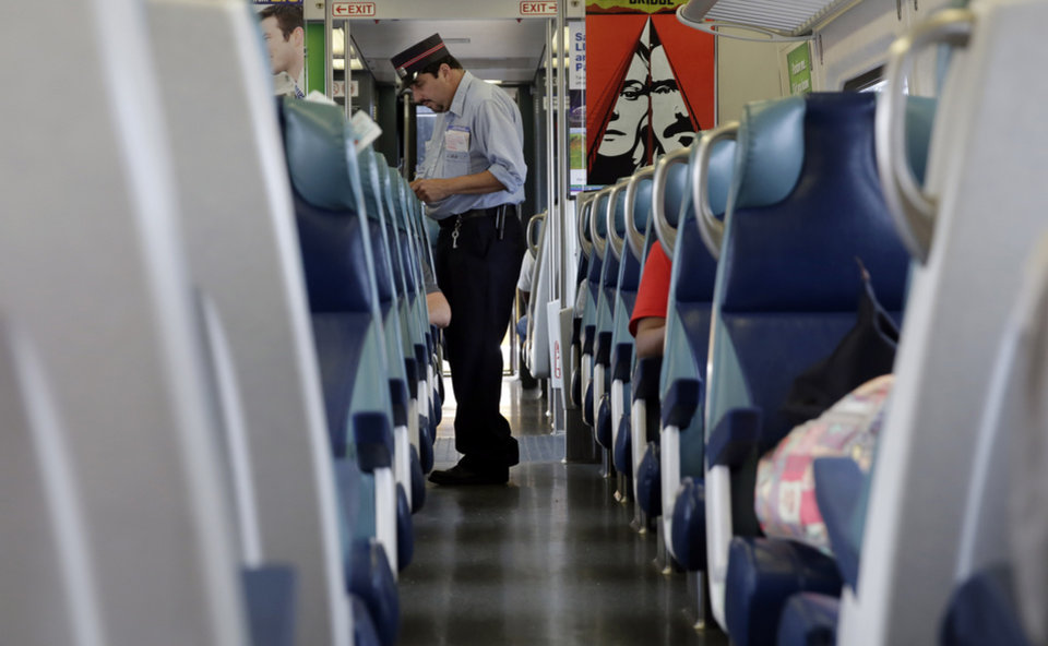 Photo - A conductor punches tickets aboard the Long Island Rail Road, in the Queens borough of New York, Wednesday, July 16, 2014. Negotiations aimed at avoiding a walkout at the nation's largest commuter railroad resumed Wednesday after Gov. Andrew Cuomo prodded both sides to find an agreement that would keep 300,000 daily riders from being forced to find alternate ways of getting in and out of New York City. (AP Photo/Richard Drew)