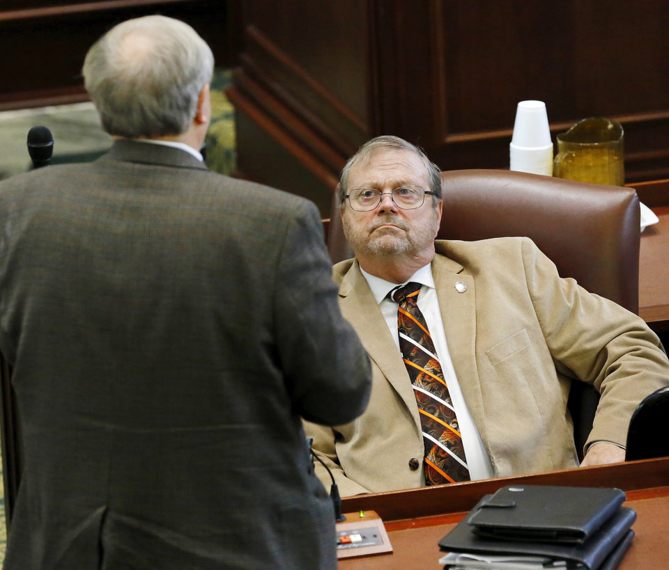Photo -  Rep. Brian Renegar, seated, listens and watches fellow Democrat legislator David Perryman engage in a discussion with another representative, questioning a motion surrounding Rep. Dan Kirby's presence on the House floor. State representatives meet for an organizational day in the House chamber on Tuesday, Jan. 3, 2017. Initial discussion focused on the resignation/non-resignation of Rep. Dan Kirby, Tulsa, who has been accused of sexual harassment with a former staff member. [Photo by Jim Beckel, The Oklahoman]