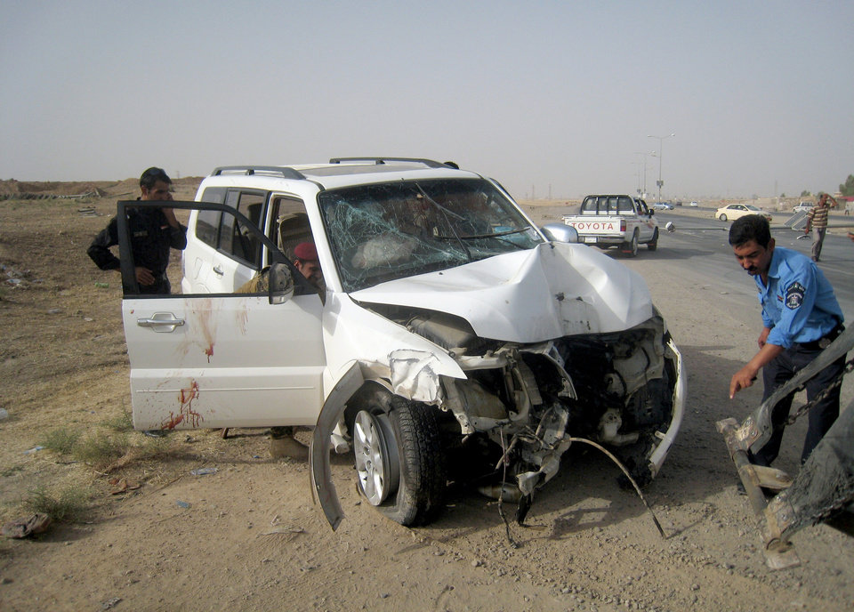 Photo - Iraqi policemen prepare to tow away a damaged sport utility vehicle following a drive-by shooting in Kirkuk, 180 miles (290 kilometers) north of Baghdad, Iraq, Monday, July 22, 2013. A provincial council member, Abdullah Sami al-Assai, was killed along with his two bodyguards in a drive-by-shooting near the center of the ethnically disputed northern city of Kirkuk, officials said. (AP Photo/Emad Matti)
