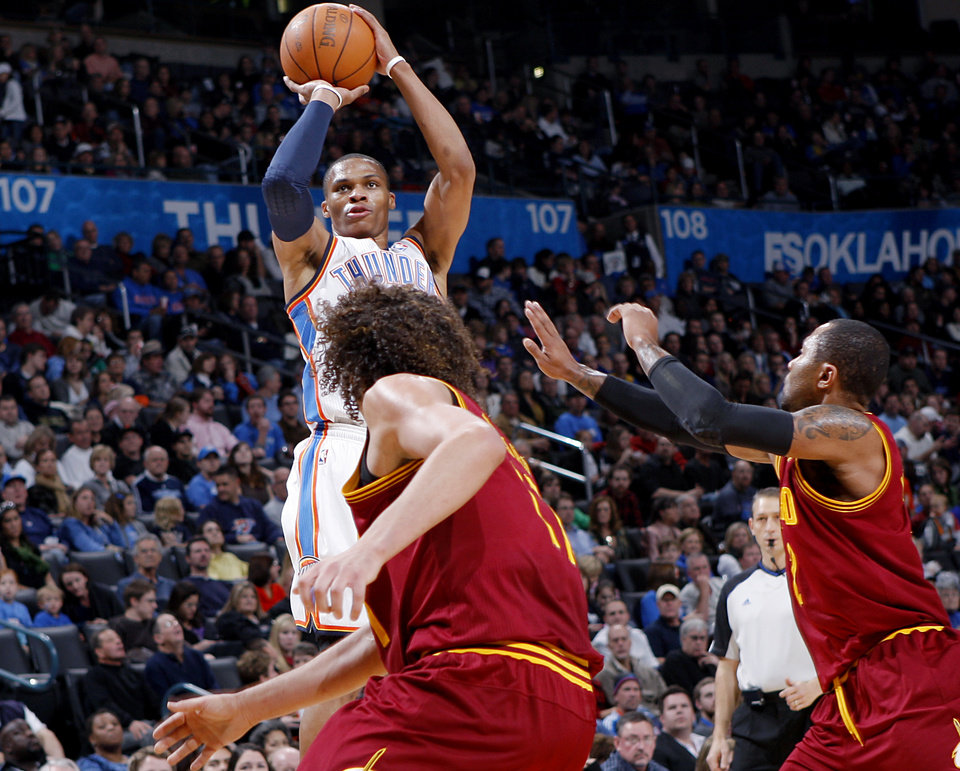 Photo - Oklahoma City's Russell Westbrook shoots over Cleveland's Anderson Varejao and Mo Williams during the first half of their NBA basketball game at the OKC Arena in Oklahoma City on Sunday, Dec. 12, 2010.  The Thunder beat the Cavaliers106-77. Photo by John Clanton, The Oklahoman