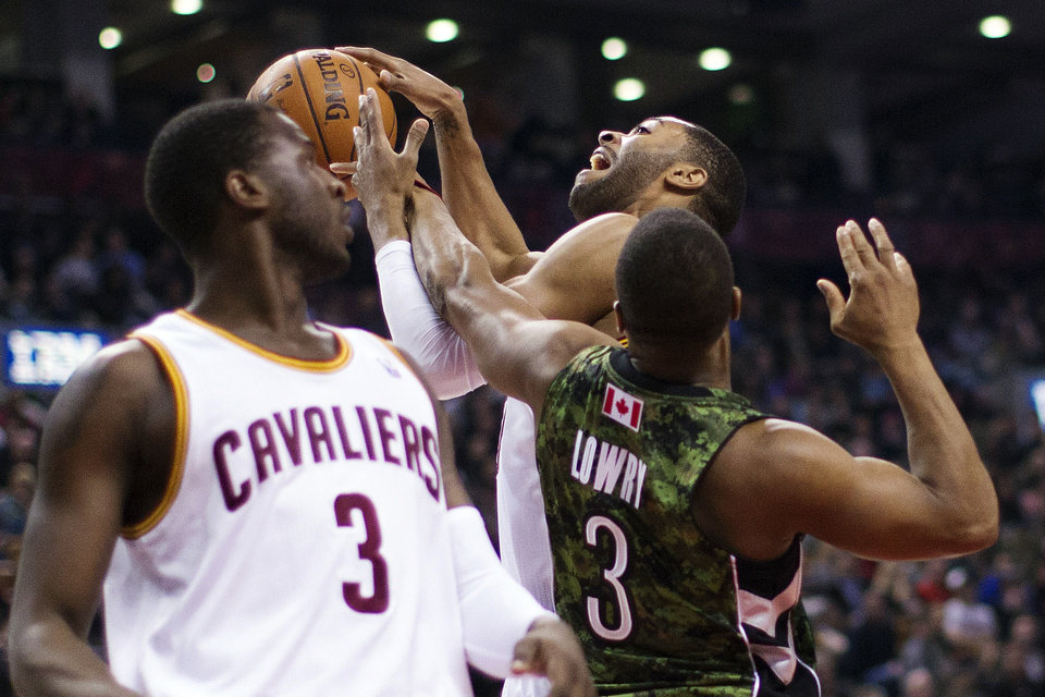 Toronto Raptors' Kyle Lowry, right, fouls Cleveland Cavaliers' Wayne Ellington, center, as Dion Waiters watches during the first half of an NBA basketball game, Saturday, Jan. 26, 2013, in Toronto. (AP Photo/The Canadian Press, Chris Young)