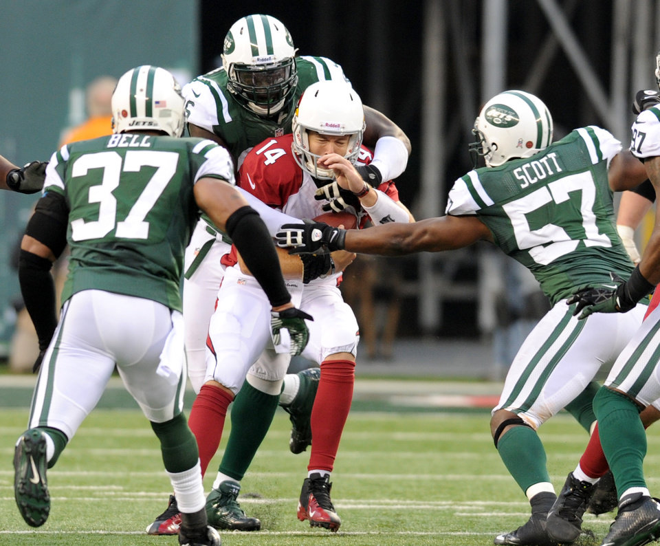 Photo - Arizona Cardinals quarterback Ryan Lindley (14) is sacked by New York Jets defensive end Muhammad Wilkerson, back, as safety Yeremiah Bell (37) and linebacker Bart Scott (57) help defend during the second half of an NFL football game, Sunday, Dec. 2, 2012, in East Rutherford, N.J. The Jets won 7-6. (AP Photo/Bill Kostroun)
