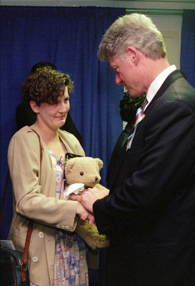 Photo - Aren Almon of Oklahoma City, clutches a teddy bear as she is greeted by President Clinton, Sunday, April 23, 1995, after a prayer service for the victims of Wednesday's deadly car bomb attack in downtown Oklahoma City. Almon's 1-year old daughter, Baylee, was killed in the attack. The President addressed an overflow crowd during the service at the Oklahoma State Fair Arena. (AP Photo/Pat Sullivan)