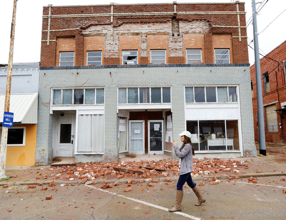 Photo - FILE - In this Monday, Nov. 7, 2016 file photo, a television reporter takes video as she walks past a damaged building in Cushing, Okla. caused by an earthquake the night before. Record-setting temblors rocked Oklahoma as the state scrambled to impose new restrictions on the disposal of wastewater in oil and gas production in one of the top stories in the state in 2016. (Jim Beckel The Oklahoman via AP, File)