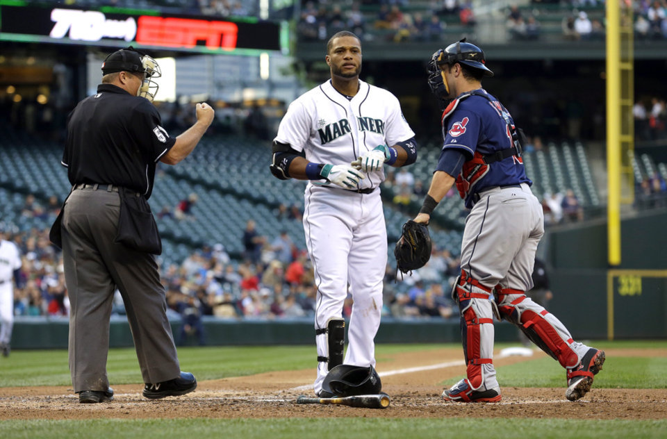 Photo - Home plate umpire Marvin Hudson, left, signals Seattle Mariners' Robinson Cano, center, out after he struck out swinging as Cleveland Indians catcher Yan Gomes stands next to them at the end of the fourth inning of a baseball game, Saturday, June 28, 2014, in Seattle. (AP Photo/Ted S. Warren)