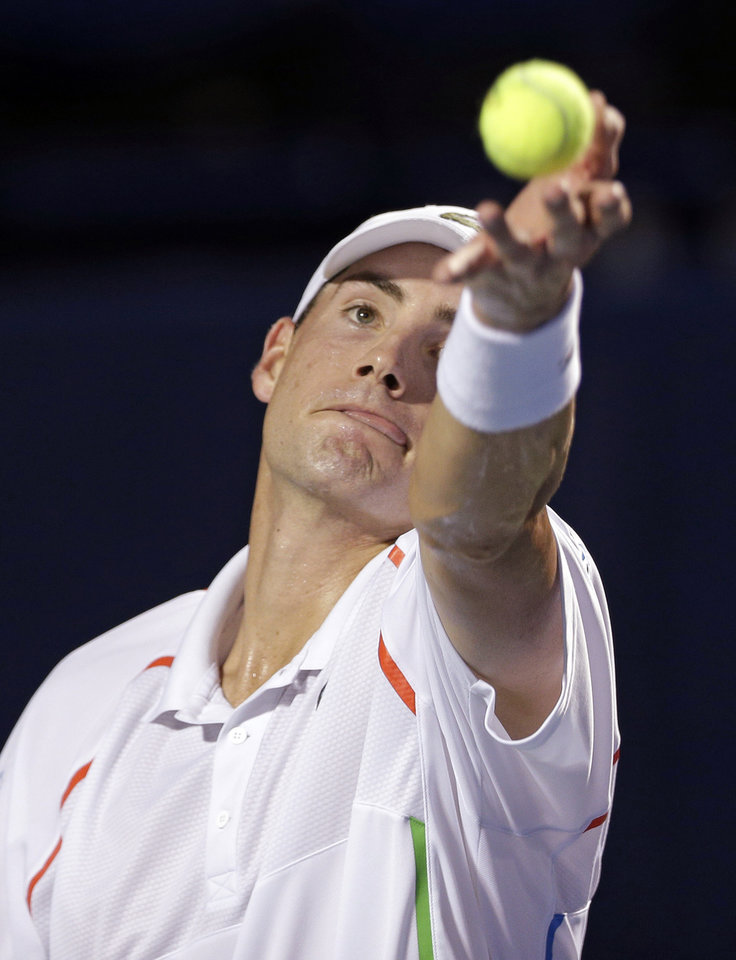Photo - John Isner prepares to serve to Mikhail Kukushkin, of Kazakhstan, during their match at the Winston-Salem Open tennis tournament in Winston-Salem, N.C., Wednesday, Aug. 20, 2014. (AP Photo/Chuck Burton)