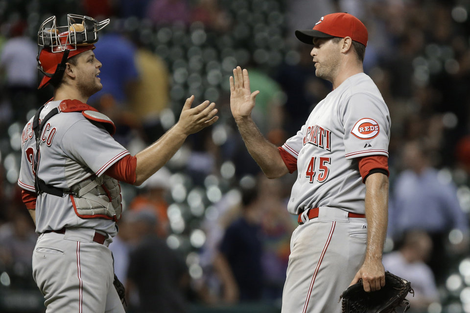 Photo - Cincinnati Reds catcher Devin Mesoraco and closing pitcher Sean Marshall (45) celebrate the Reds' 10-0 win over the Houston Astros in a baseball game Tuesday, Sept. 17, 2013, in Houston. (AP Photo/Pat Sullivan)