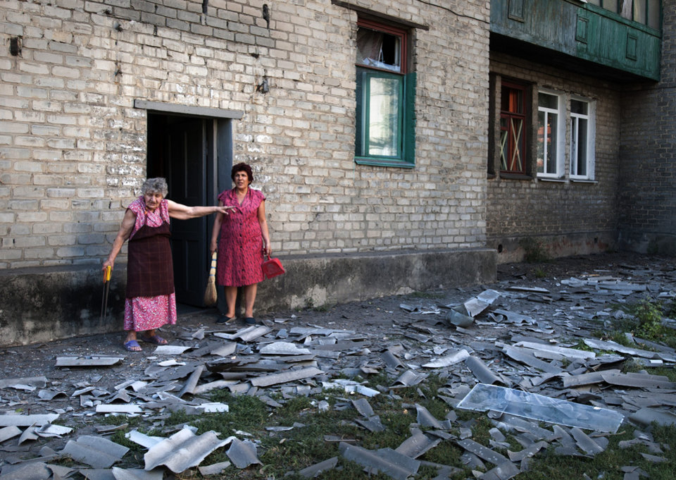 Photo - In this photo taken Wednesday, Aug. 27, 2014, local residents stand near the building where they live after a shelling in Donetsk, eastern Ukraine. Two columns of Russian tanks and military vehicles fired Grad missiles at a border post in southeastern Ukraine, then rolled into the country Thursday as Ukraine's overmatched border guards fled, a top Ukrainian official said. (AP Photo/Antoine E.R. Delaunay)