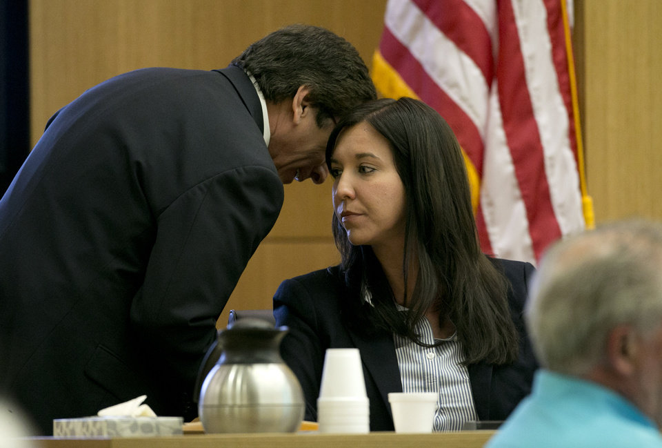 Photo - Prosecutor Juan Martinez whispers ion the ear of Dr. Janeen DeMarte an expert witness for the prosecution during the Jodi Arias trial at Maricopa County Superior Court in Phoenix on Tuesday, April 16, 2013. Defense attorneys rested their case Tuesday after about 2 1/2 months of testimony aimed at portraying Arias as a domestic violence victim who fought for her life the day she killed her one-time boyfriend.  (AP Photo/The Arizona Republic, David Wallace, Pool)
