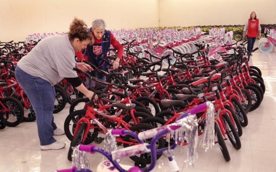 Photo -  The Salvation Army Women's Auxiliary members arrange assembled bicycles for boys and girls during the 2018