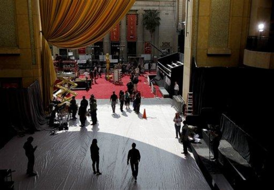 People bustle about the red caret at the entrance of the Kodak Theatre as preparations continue for the 84th Academy Awards in Los Angeles on Saturday,  Feb. 25, 2012. The Oscars will be held on Sunday. (AP Photo/Amy Sancetta)
