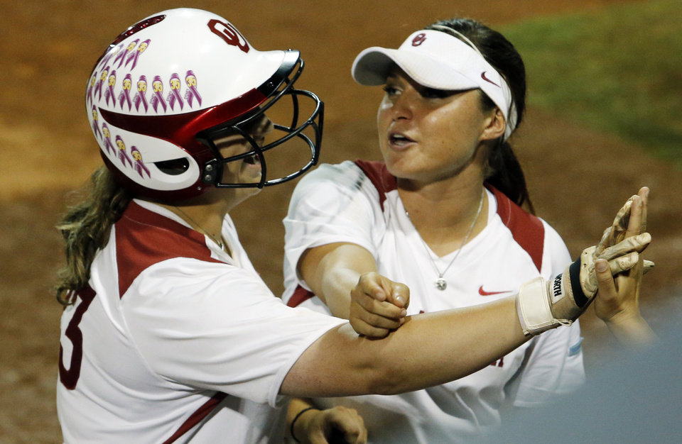 Photo - Oklahoma's Erin Miller, right, points to the spot where Brittany Williams' home run went over the fence as the University of Oklahoma Sooner (OU) softball team plays Tennessee in the first game of the NCAA super regional at Marita Hynes Field on May 23, 2014 in Norman, Okla. Photo by Steve Sisney, The Oklahoman