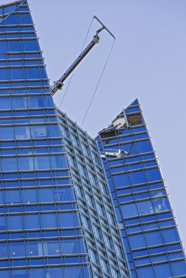 Photo - Damage to the top of the Devon Tower after crews rescued two workers off of a broke lift on top of the build in downtown Oklahoma City, Okla. on Tuesday, May 14, 2019.  [Chris Landsberger/The Oklahoman]