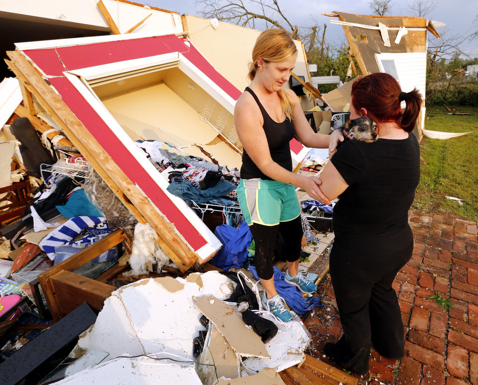 Alli Christian, left, returns Jessica Wilkinson\'s dog Bella to her after finding her among the wreckage of Wilkinson\'s home shortly after a tornado struck near 156th street and Franklin Road on Sunday, May 19, 2013 in Norman, Okla. Photo by Steve Sisney, The Oklahoman