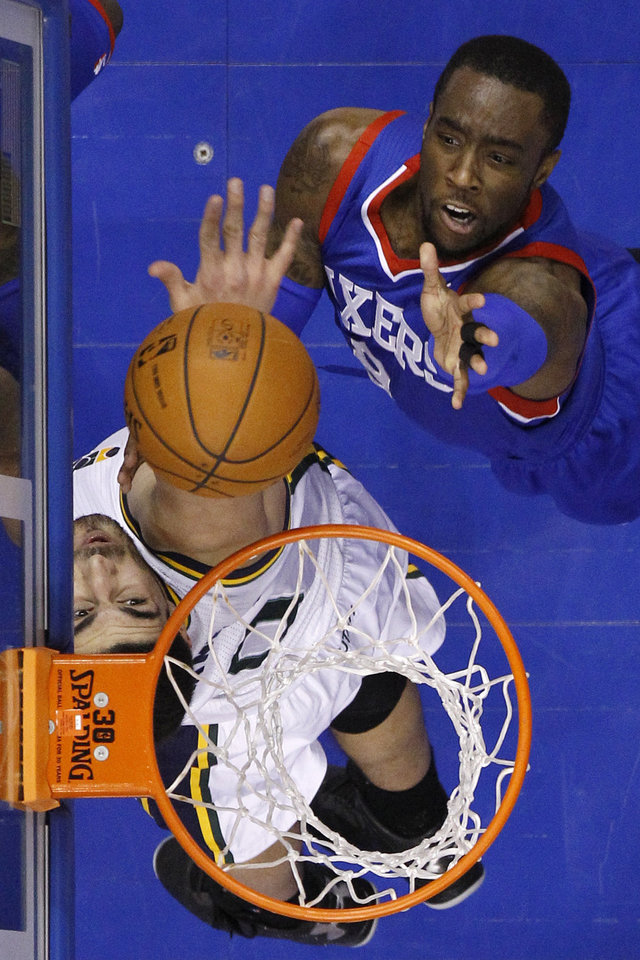 Photo - Philadelphia 76ers' Tony Wroten, top, battles for a rebound with Utah Jazz's Enes Kanter during the first half of an NBA basketball game on Saturday, March 8, 2014, in Philadelphia. (AP Photo/Matt Slocum)