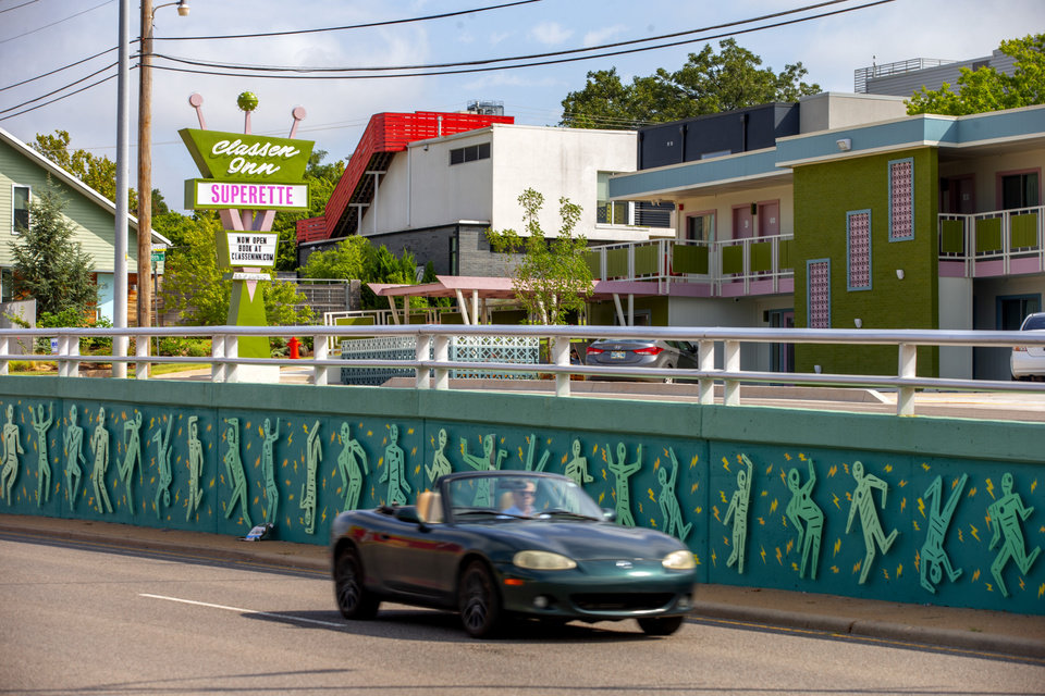 "Photo -  A car passes the recently installed ""Birdwatching OKC Lightning Thunder Dance Party,"" a $38,000 art installation by Joe Slack that was funded by Oklahoma City Beautiful as part of its 50th anniversary celebrations. The mural on the Classen divider complements the color scheme of the Classen Inn in the background. [BRYAN TERRY/THE OKLAHOMAN]"