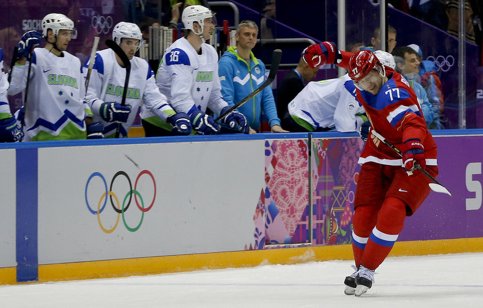 Photo - Russia defenseman Anton Belov reacts after scoring a goal against Slovenia in the third period of a men's ice hockey game at the 2014 Winter Olympics, Thursday, Feb. 13, 2014, in Sochi, Russia. (AP Photo/Julio Cortez)
