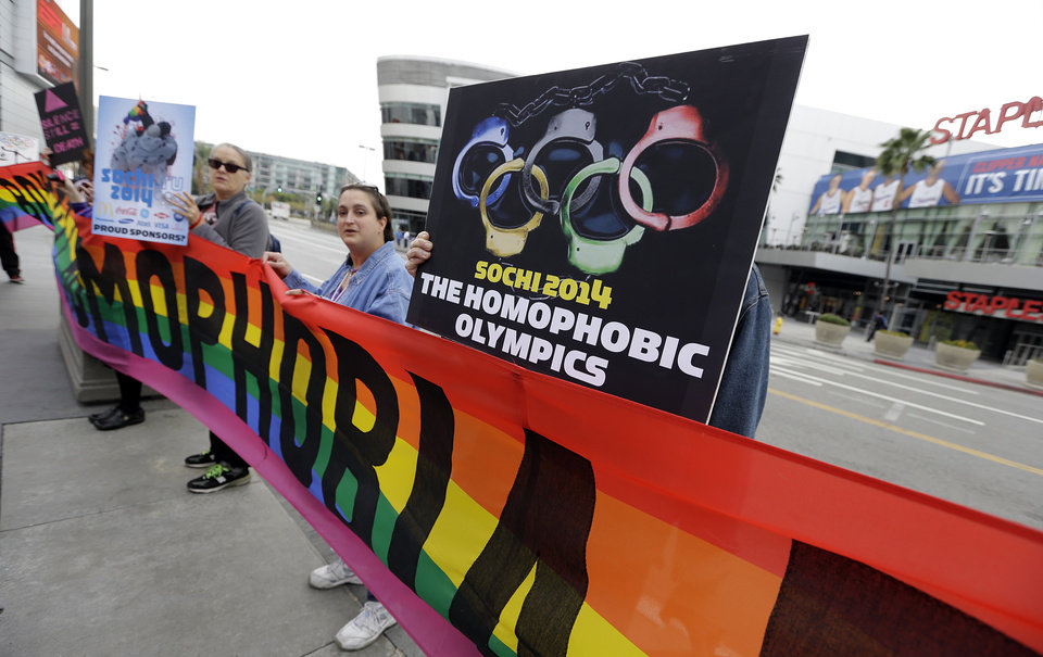 Photo - Demonstrators from a coalition of gay rights organizations, religious and political groups protest the treatment of gays in Russia, whose coastal city of Sochi hosts the 22nd Olympic Winter Games, outside the final stop of the