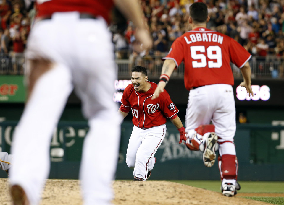 Photo - Washington Nationals' Wilson Ramos center celebrates with catcher Jose Lobaton, and others after Ramos hit the game winner during the ninth inning of a baseball game against the Pittsburgh Pirates at Nationals Park, Saturday, Aug. 16, 2014, in Washington. The Nationals won 4-3. (AP Photo/Alex Brandon)