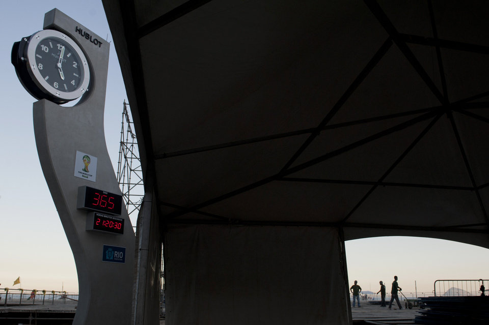 The official 2014 World Cup countdown clock, left, has stopped counting time, in Rio de Janeiro, Brazil, Thursday, Aug. 1, 2013. Although there's less than 11 months before the 2014 World Cup begins, the clock set up by local organizers at Copacabana Beach still shows there are 365 days to go before the showcase event. (AP Photo/Nicolas Tanner)
