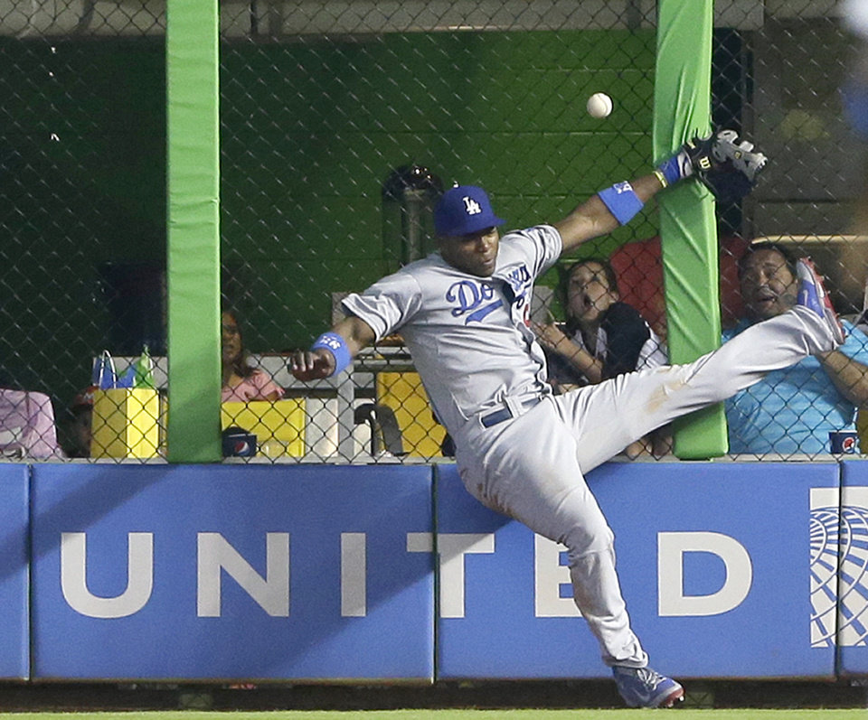 Photo - Los Angeles Dodgers right fielder Yasiel Puig is unable to catch a ball at the fence hit by Miami Marlins' Jeff Baker for a double, during the ninth inning of a baseball game, Sunday, May 4, 2014 in Miami. Adeiny Hechavarria scored on the play as the Marlins defeated the Dodgers 5-4. (AP Photo/Wilfredo Lee)