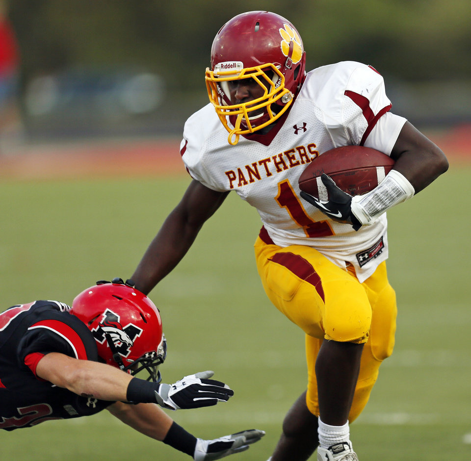 Putnam City North's Tae Moore (1) avoids Mustang's Tanner Golden (33) on a carry during a high school football game between Mustang and Putnam City North in Mustang, Okla., Friday, Sept. 7, 2012. Photo by Nate Billings, The Oklahoman