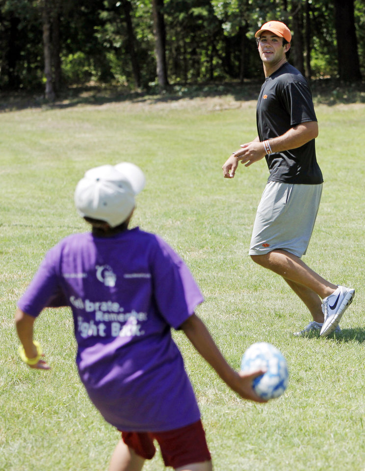 Photo - Camper Emilio Valdez, 11, tosses a football to OSU quarterback Zac Robinson at the American Cancer Society's Camp Live-A-Dream in Guthrie, Okla., Wednesday, June 17, 2009. Photo by Nate Billings, The Oklahoman