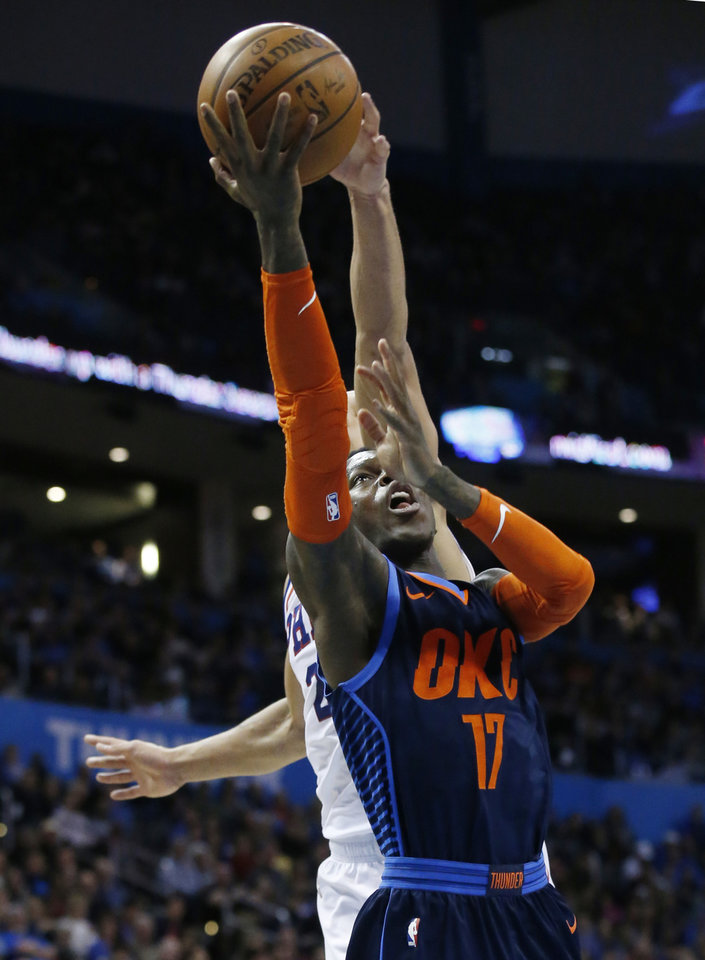 Photo - Oklahoma City Thunder guard Dennis Schroeder (17) shoots in front of Philadelphia 76ers guard Ben Simmons during the second half of an NBA basketball game Thursday, Feb. 28, 2019, in Oklahoma City. (AP Photo/Sue Ogrocki)