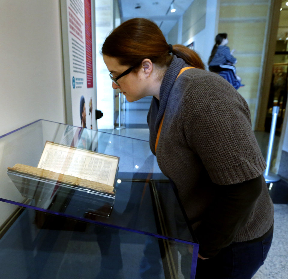 Photo -  Robin Murphy, an English teacher at East Central University in Ada, studies a page from Hamlet, included in Shakespeare's First Folio, now on display at the Sam Noble Oklahoma Museum of Natural History. [PHOTO BY STEVE SISNEY, THE OKLAHOMAN]