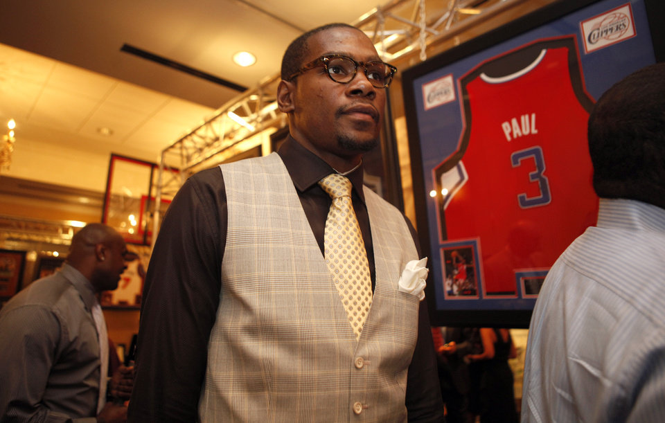 Photo - Oklahoma City's Kevin Durant walks looks at items available in a silent auction during the KD 35 Ball benefiting the Kevin Durant Family Foundation at the Skirvin Hilton Hotel in Oklahoma City, Saturday, March 31, 2012. Photo by Sarah Phipps The Oklahoman