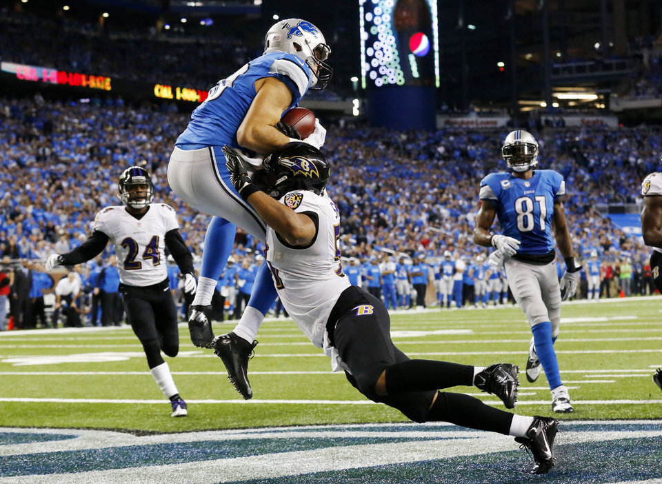Photo - Detroit Lions tight end Joseph Fauria, left, defended by Baltimore Ravens inside linebacker Daryl Smith catches a 14-yard pass for a touchdown during the fourth quarter of an NFL football game in Detroit, Monday, Dec. 16, 2013. (AP Photo/Paul Sancya)