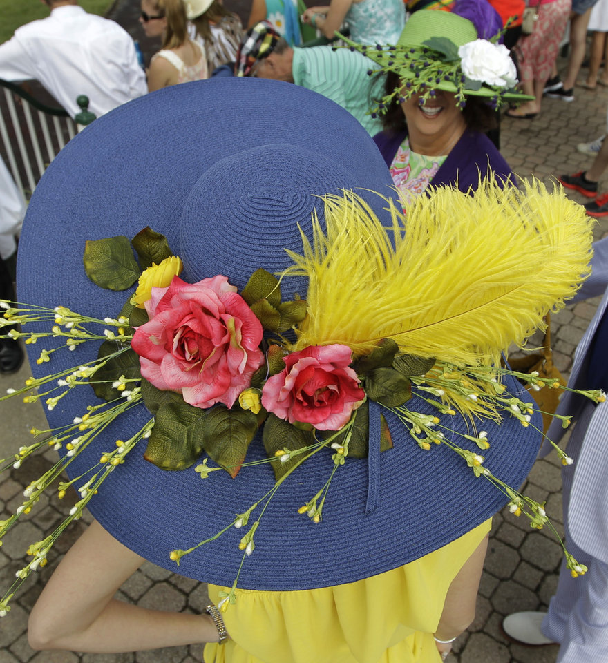 Photo - Kimberly Scott, left, from Albany, Ga., chats with a friend in the paddocks before the 138th Kentucky Derby horse race at Churchill Downs Saturday, May 5, 2012, in Louisville, Ky. (AP Photo/Michael Conroy)  ORG XMIT: DBY112