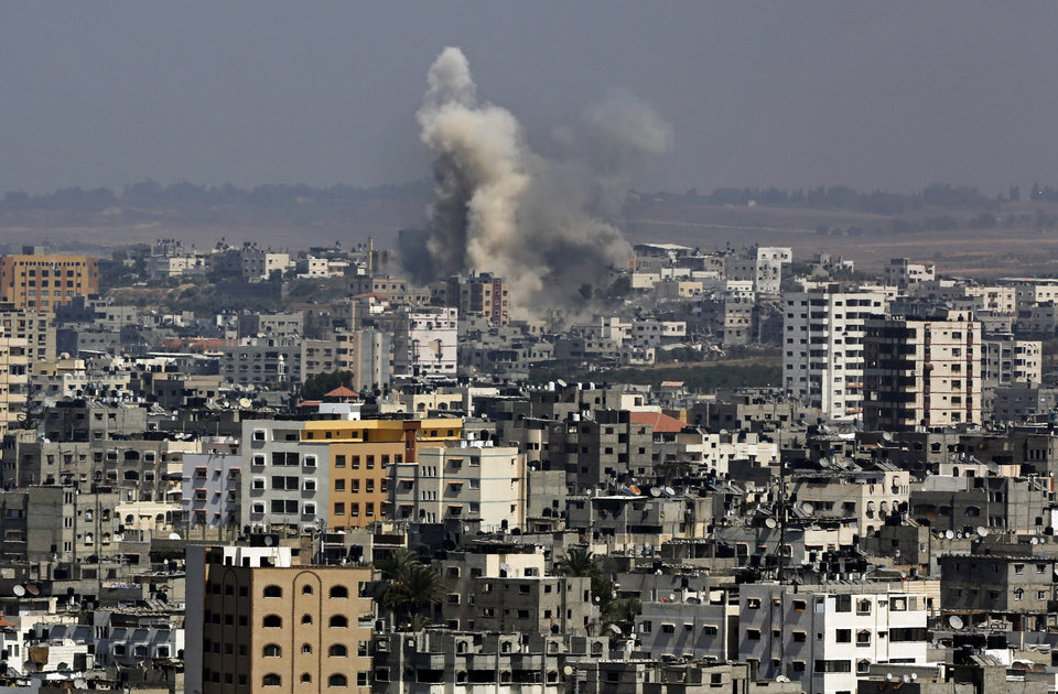 Photo - Smoke and dust rise after an Israeli strike hits in Gaza City, northern Gaza Strip, Monday, Aug. 25, 2014. (AP Photo/Adel Hana)