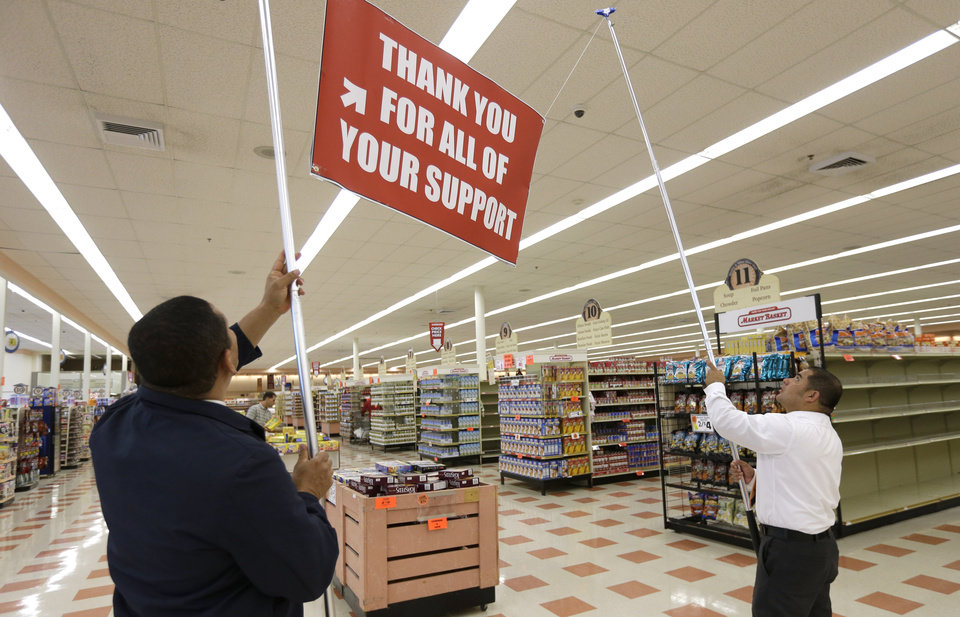 Photo - Market Basket employees Eduin Uribe, left, and Kevin Pineda hoist a sign at a Market Basket supermarket location, Thursday, Aug. 28, 2014, in Chelsea, Mass. A six-week standoff between thousands of employees of the New England supermarket chain and management has ended with the news that beloved former CEO Arthur T. Demoulas is back in control after buying the entire company. (AP Photo/Steven Senne)