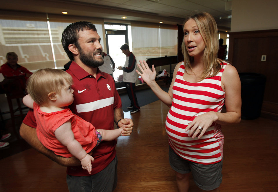 Photo - Wrestler Jared Frayer holds his daughter Khloe, 18-months, as wife Nicole (35 weeks pregnant) explains on Thursday, July 5, 2012 in Norman, Okla.  that her due date is two days after Jared is due to compete in the Olympics.  Frayer is among six athletes from the University of Oklahoma who have qualified for the 2012 London Olympics in track and field, wrestling and men's gymnastics.   Photo.  Photo by Steve Sisney, The Oklahoman
