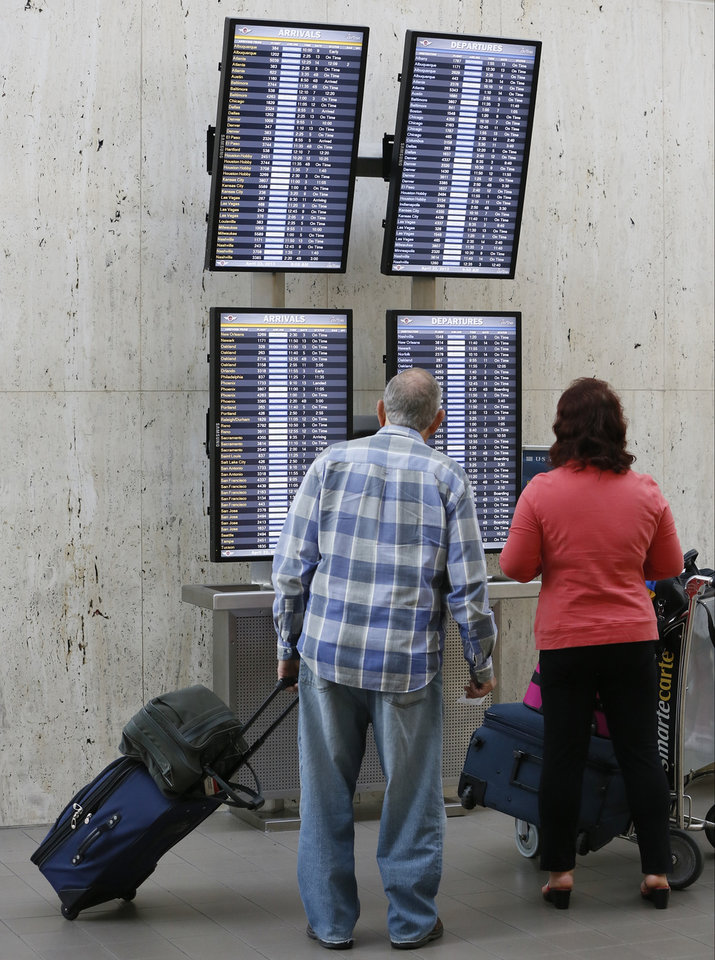 Photo - Traveler Jay Mortimer, left,  checks his flight status at LAX International airport in Los Angeles Monday, April 22, 2013.  The FAA said late Sunday night that staffing cuts were causing delays averaging more than three hours for flights arriving at Los Angeles International Airport.   (AP Photo/Damian Dovarganes)
