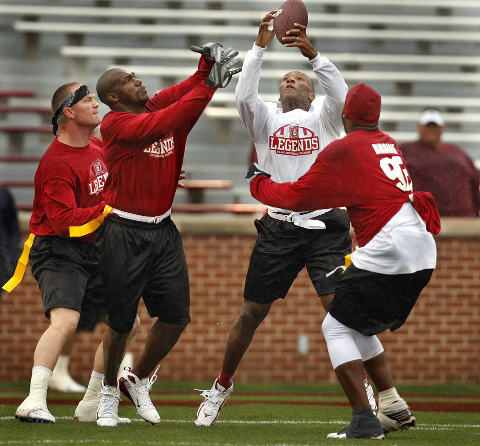 Photo - Cream Team member Danny Wilson goes up for a pass defended by Brian Bosworth, Rufus Alexander and Larry Birdine during the OU Legends flag football game for the University of Oklahoma (OU) Sooners at Gaylord Family/Oklahoma Memorial Stadium on Saturday, April 17, 2010, in Norman, Okla.  Photo by Steve Sisney, The Oklahoman