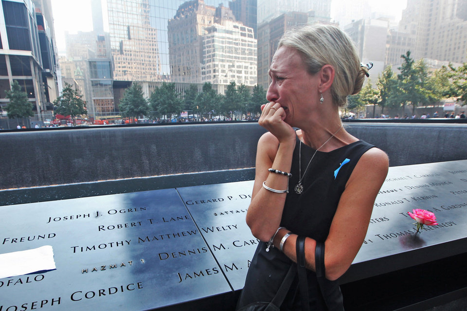 Photo - Carrie Bergonia of Pennsylvania looks over the name of her fiancé, firefighter Joseph Ogren, at the 9/11 Memorial during ceremonies marking the 12th anniversary of the 9/11 attacks on the World Trade Center in New York, Wednesday, Sept 11, 2013.  (AP Photo/Chris Pedota, Pool)