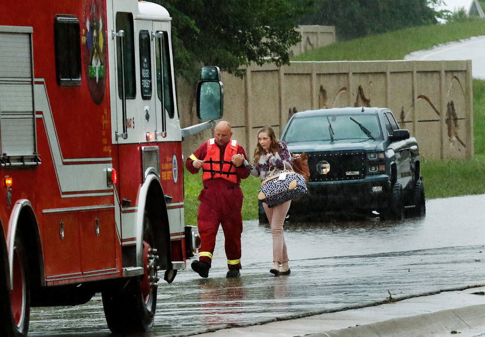 Photo - An Oklahoma City firefighter assists a woman as she walks from a stranded vehicle on a flooded ramp from southbound I-235 near NW 23 Street. Brief periods of heavy rain caused road flooding and created hazardous driving conditions around 7 pm Saturday, May 23, 2015.  Oklahoma City police used their vehicles to barricade all directions of traffic at NW 23 and Broadway, preventing vehicles from driving into high and rushing water. Photo by Jim Beckel, The Oklahoman.